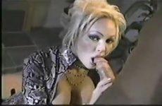 Hitsig kijkend in de videocamera geeft zij de grote jongeheer een blowjob beurt