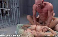 Zijn zwoel eega naait de gevangene tegenover hem