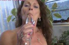 Deze geile huisvrouw mastubeerd met een glazen dildo